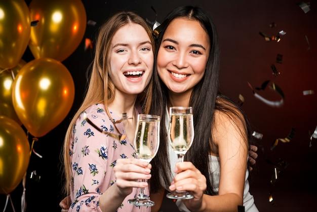 Colpo medio degli amici che tengono i vetri del champagne