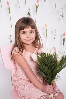 Colpo medio dei tulipani graziosi della tenuta della ragazza