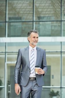 Colpo medio del dirigente d'azienda intelligente in abbigliamento da lavoro in piedi fuori dall'edificio per uffici per avere il suo caffè da asporto