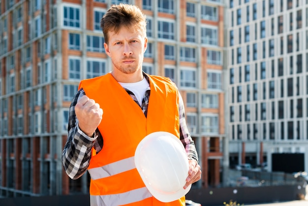 Colpo medio del muratore arrabbiato che esamina macchina fotografica