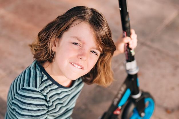 Colpo medio del ragazzo con scooter