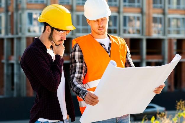 Colpo medio dell'architetto e dell'ingegnere che esaminano i piani
