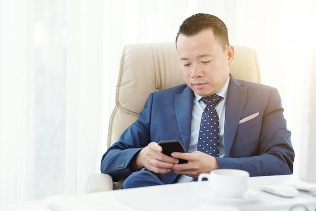 Colpo medio dell'imprenditore che manda un sms ad un messaggio nella sua poltrona dell'ufficio