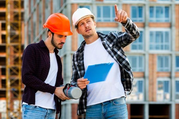 Colpo medio dell'ingegnere e dell'architetto che esaminano lavagna per appunti