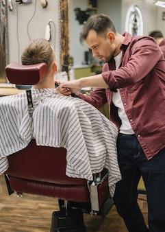 Colpo medio dell'uomo al barbiere
