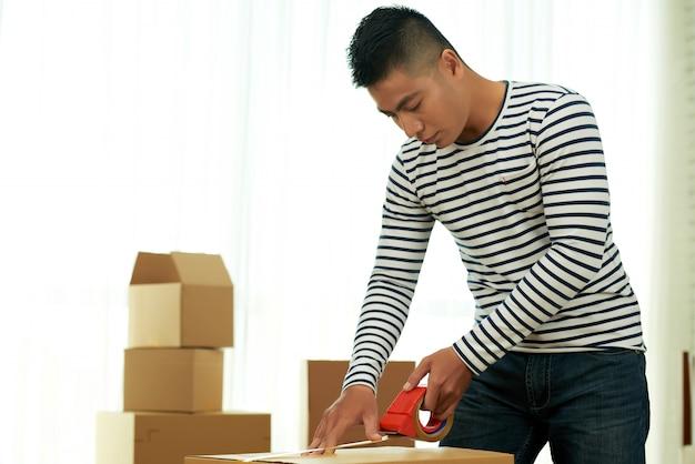 Colpo medio dell'uomo asiatico che imballa una scatola con nastro adesivo