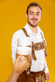 Colpo medio dell'uomo con la pinta di birra