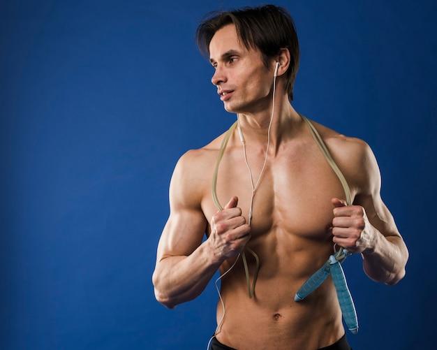 Colpo medio dell'uomo muscoloso senza camicia con le cuffie