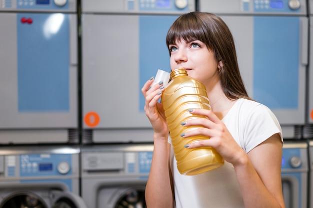 Colpo medio della bottiglia detergente sentente l'odore della donna