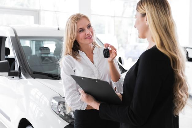 Colpo medio della donna che compra nuova automobile
