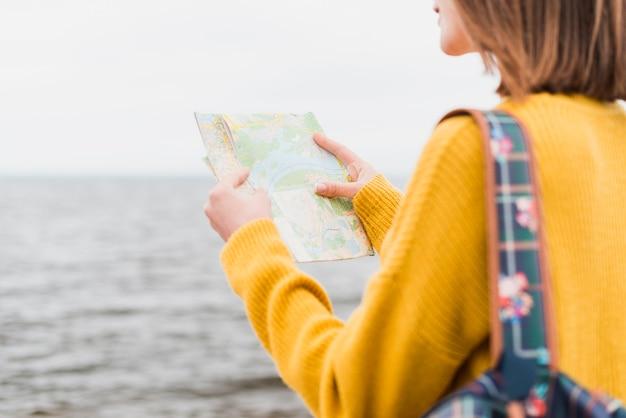 Colpo medio della donna che controlla mappa