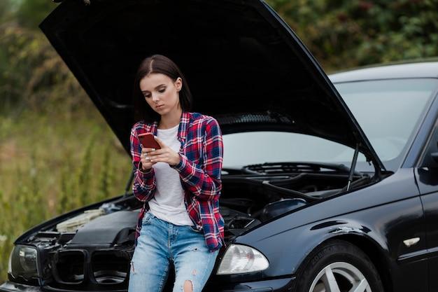 Colpo medio della donna che controlla telefono