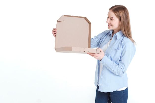 Colpo medio della donna che esamina un contenitore di pizza