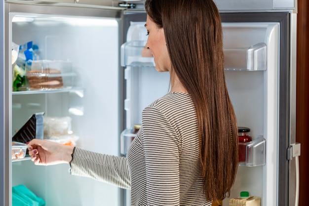 Colpo medio della donna che guarda nel frigorifero