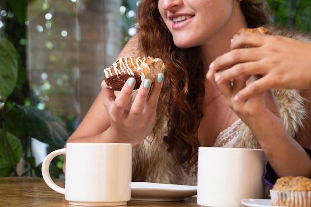 Colpo medio della donna che mangia i dolci