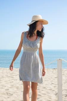 Colpo medio della donna che osserva via la spiaggia