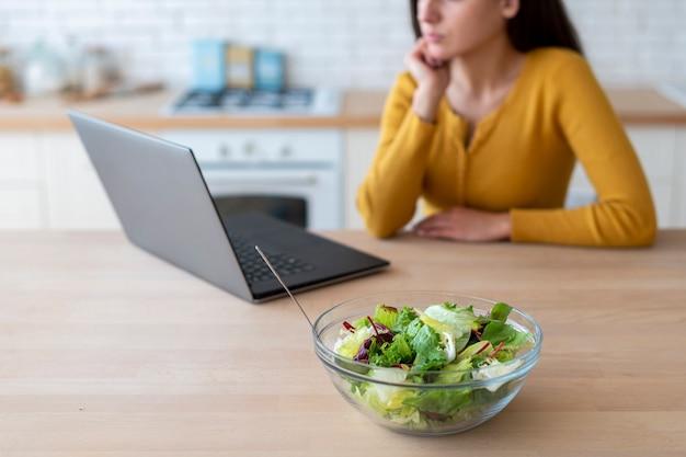 Colpo medio della donna che per mezzo del computer portatile