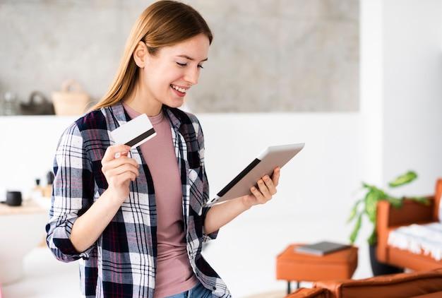 Colpo medio della donna che tiene la sua carta di credito e che esamina la compressa