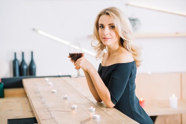 Colpo medio della donna che tiene vino di vetro