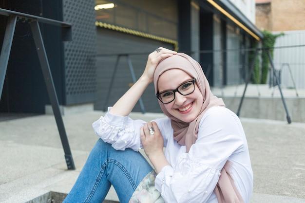 Colpo medio della donna con gli occhiali sorridente