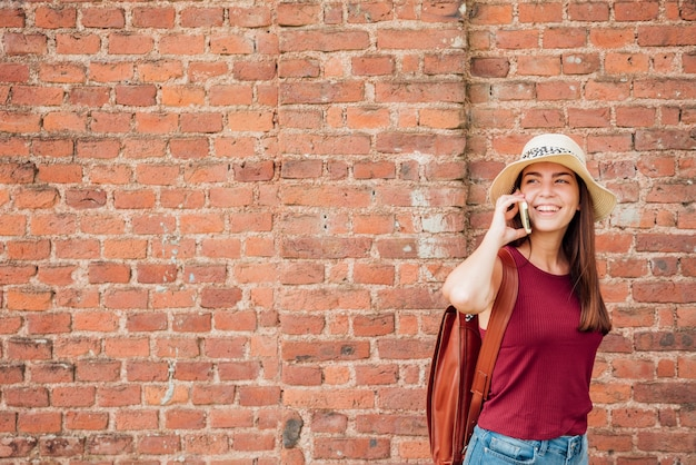 Colpo medio della donna con il fondo del muro di mattoni
