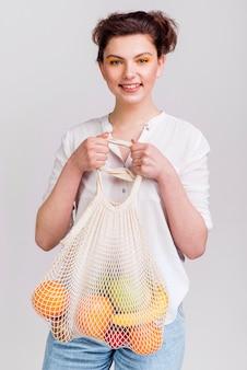 Colpo medio della donna con il sacchetto di frutta