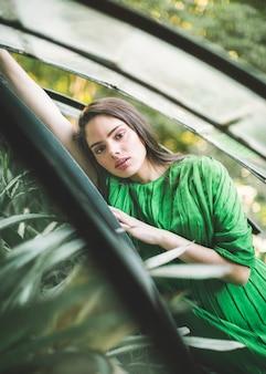 Colpo medio della donna in abito verde