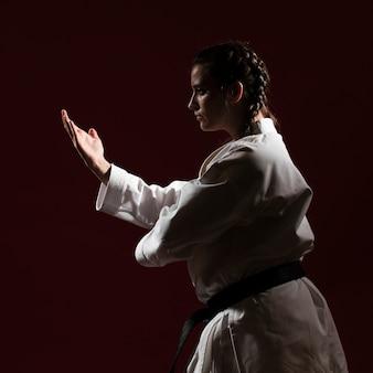 Colpo medio della donna in uniforme bianca di karatè