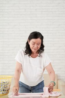 Colpo medio della donna senior che piega i vestiti puliti