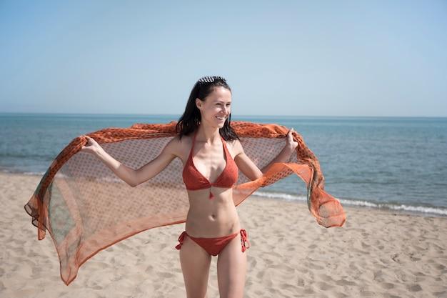 Colpo medio della donna sorridente che osserva via la spiaggia
