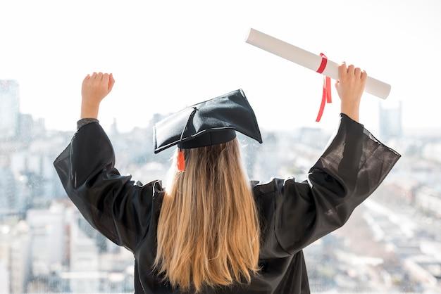 Colpo medio della giovane donna che è fiero alla sua laurea