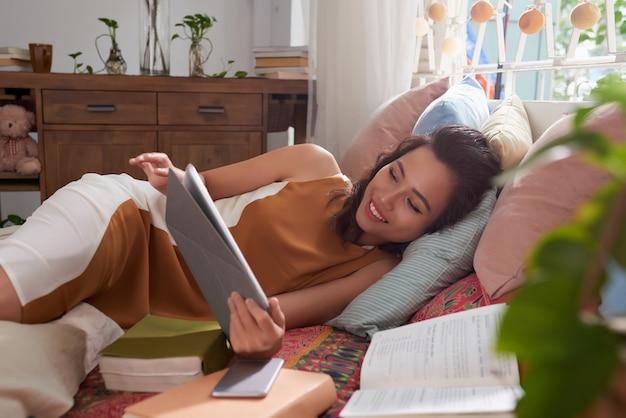 Colpo medio della giovane donna che riposa a letto leggendo il libro elettronico