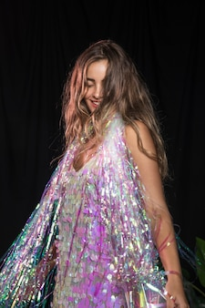 Colpo medio della ragazza che balla e con uno scialle di scintillii per la festa