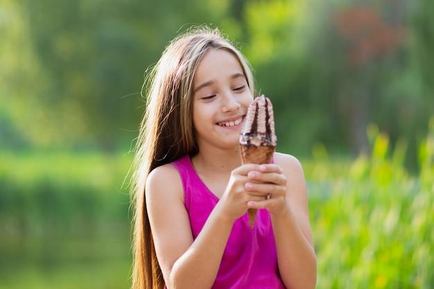 Colpo medio della ragazza con gelato al cioccolato