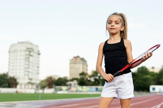 Colpo medio della ragazza con la racchetta da tennis rossa