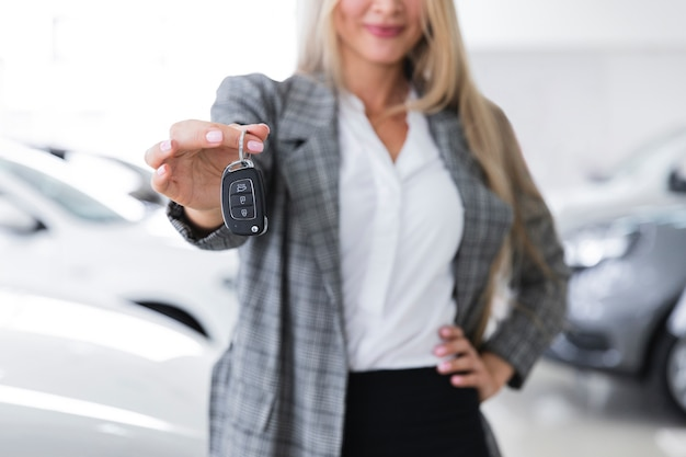 Colpo medio delle chiavi dell'automobile della tenuta dell'autista
