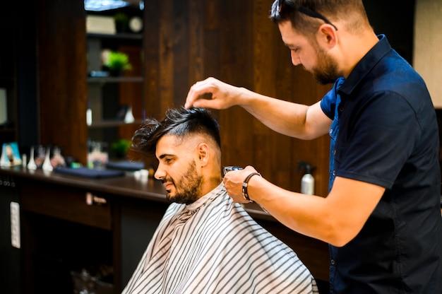 Colpo medio dello stilista che organizza i capelli del cliente