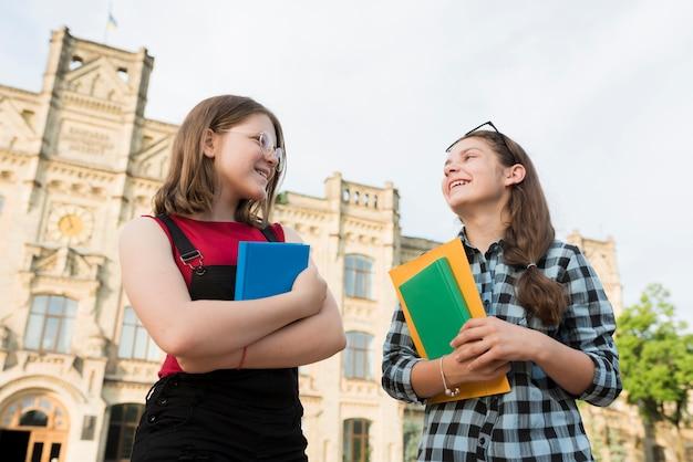 Colpo medio di angolo basso di conversazione delle ragazze adolescenti