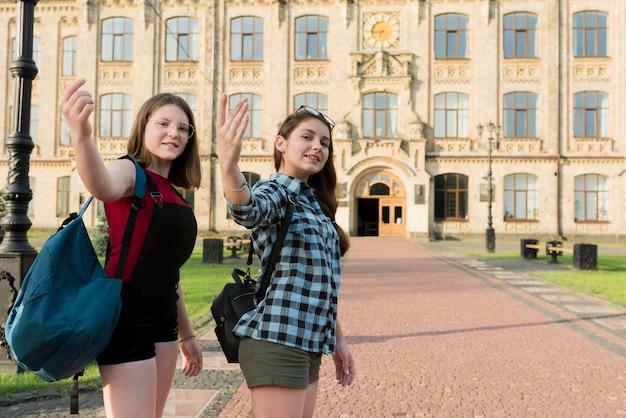 Colpo medio di due ragazze del liceo che guarda l'obbiettivo