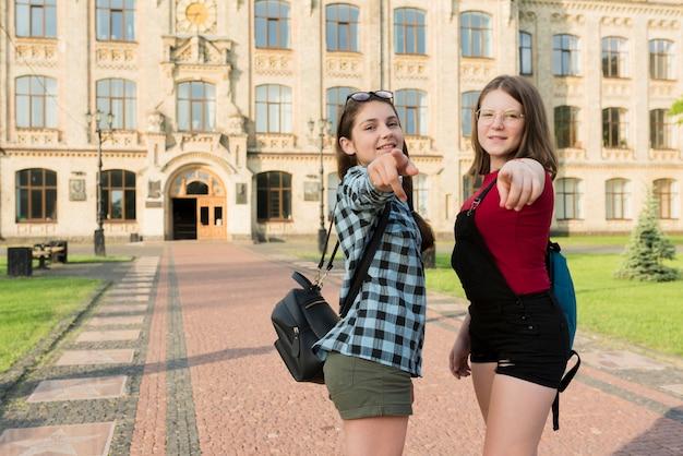 Colpo medio di due ragazze del liceo che indicano alla macchina fotografica