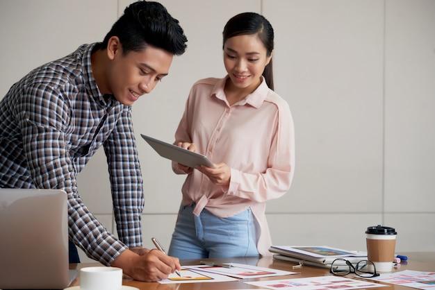 Colpo medio di giovani asiatici coworking su un progetto di avvio
