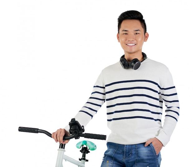 Colpo medio di giovani pantaloni a vita bassa asiatici che stanno accanto al suo sorridere della bici