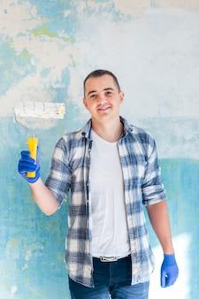 Colpo medio di un uomo sorridente che tiene un rullo di vernice