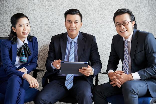 Colpo medio di una squadra di affari che si siede nell'ufficio con il pc della compressa