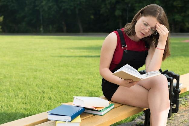 Colpo medio di vista laterale della ragazza della high school che legge sul banco