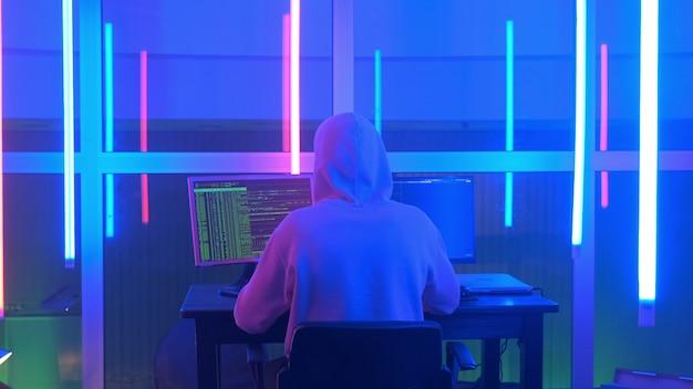 Colpo medio di vista posteriore del pirata informatico criminale che lavora alla sera sul computer in grande ufficio