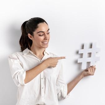Colpo medio donna che punta all'oggetto hashtag
