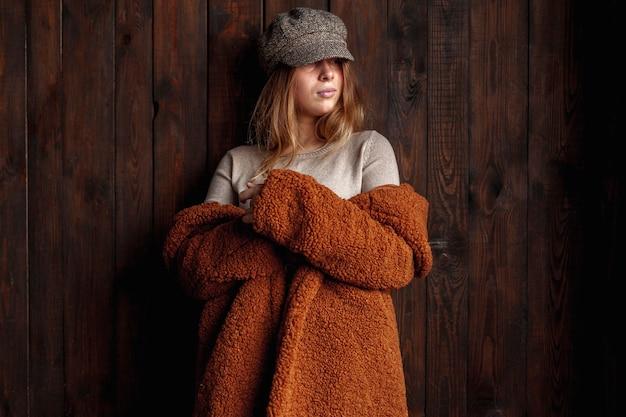 Colpo medio donna con cappello e cappotto al chiuso