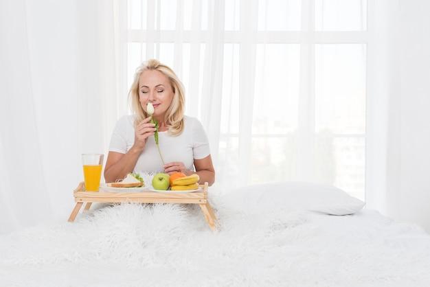 Colpo medio donna con colazione a letto e fiore