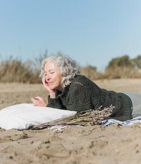Colpo medio donna con cuscino sulla spiaggia